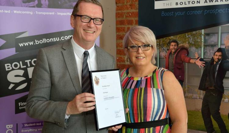 Assistant teaching professor Neil Dougan was presented with a certificate from the pro-vice-chancellor